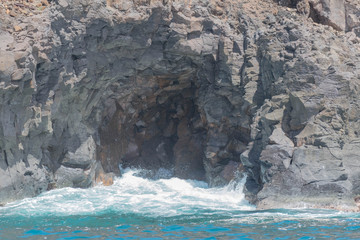 Ocean and a small wave entering a natural lava cave