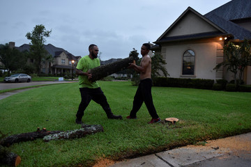 Jovannie Magana and Obama Soto remove tree limbs that were downed by a tornado that spun off of Hurricane Harvey after the storm made landfall on the Texas Gulf coast