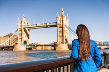 Wall Mural - Tower Bridge London city travel woman tourist girl at Europe destination landmark famous attraction. Woman traveling in autumn season .