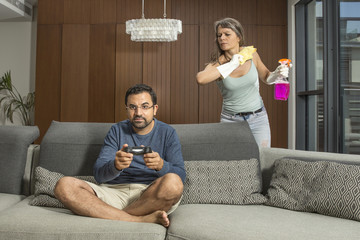 arab man playing a video game while woman is cleaning around him