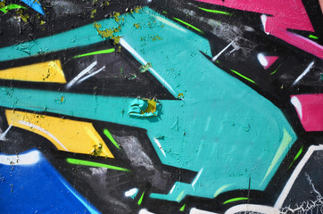 The old wall, painted in color graffiti drawing green aerosol paints. Background image on the theme of drawing graffiti and street art