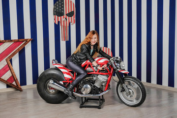 Young attractive woman dressed in leather sitting on a motorcycle in the studio.