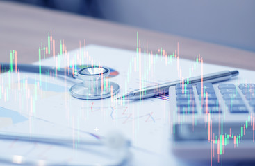 double exposure of stock graph market with stethoscope,pen and calculator lay on paperwork,investment risk concept