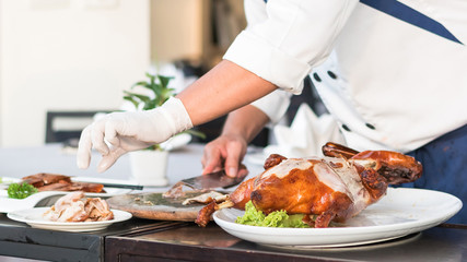 Chef preparing Chinese Peking Duck on dishes for food serving on restaurant table