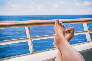 Wall Mural - Cruise vacation travel woman relaxing with feet on balcony ship deck at view of ocean on honemoon boat voyage destination. Relaxation lifestyle.