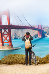 San Francisco Golden Gate Bridge biking tourist with bicycle taking pictures of view on West Coas, California, United States of America. USA travel people lifestyle.