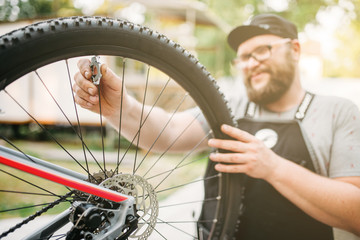 Bicycle mechanic in apron adjusts bike spokes