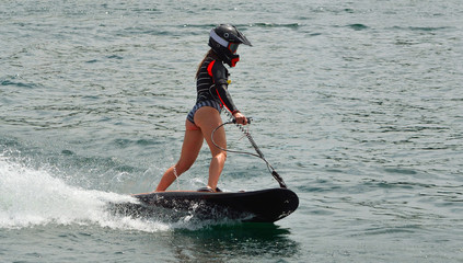 Garden Poster Water Motor sports Female Motosurf Competitor moving at speed.