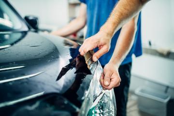 Worker hands wraps car hood in protective coating