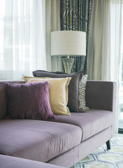 Stylish living room with purple sofa and colorful pillows