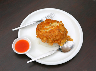 An omelet is a dish made from beaten eggs quickly cooked with butter or oil in a frying pan. served with steamed rice on plate that is Thai Style Fast food.