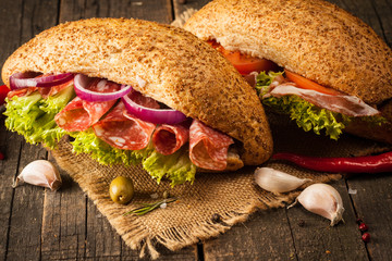 Close-up photo of a club sandwich. Sandwich with meet, prosciutto, salami, salad, vegetables, lettuce, tomato, onion and mustard on a fresh sliced rye bread on wooden background. Olives background.
