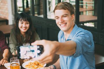 Three Happy Friends Taking Selfie Photo in Pub