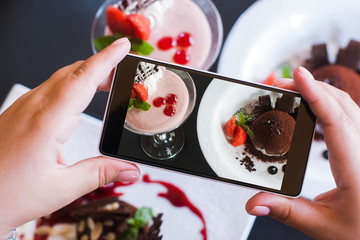 Food photography of sweet desserts by smartphone in restaurant. Creamy strawberry souffle and chocolate fondant, photo shoot and new technology, close up pov picture