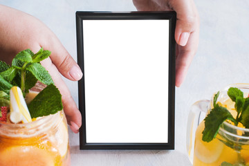 Picture frame tenderly holding by hands with fresh fruit cocktails in front. Food blogs, menu and recipes for web sites of cafe and restaurant, close up picture with copy space