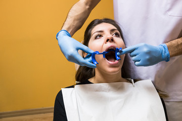 Unrecognizable dentist applying mouth expander to client for examine in cabinet.