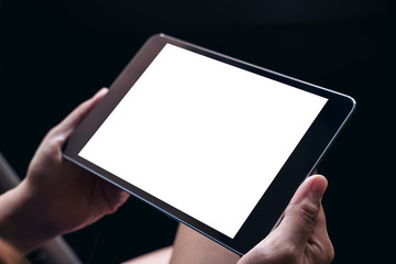 Mockup image of a woman's hands holding black tablet pc with blank white screen on thigh in black background