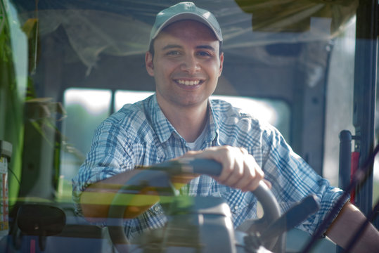 Smiling farmer driving an harvesting machine