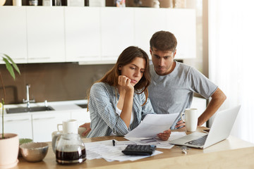 Picture of young wife and husband in kitchen having concentrated looks while reading notification from bank concerning their loan application. Caucasian couple calculating expenses in the morning