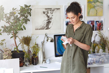 Indoor shot of gorgeous beautiful brunette young woman designer typing text message on mobile phone, shopping online, ordering paint, canvas or frame. People, art, creativity and technology concept