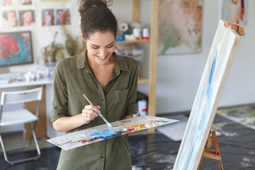 Glad woman working as painter, standing near easel, holding paint brush, creating abstract picture with colorful oils, having good mood and inspiration. Female drawing on canvas. Art concept