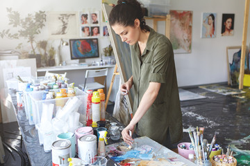 Busy female painter taking oil colors while standing near table with oils, working in art studio, going to draw sea landscape or portrait. Attractive young woman working on canvas at workshop