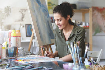 Picture of cute female artist sitting at table, surrounded with watercolors, drawing something at easel, having happy expression. Brunette young woman being busy with creative work at workshop