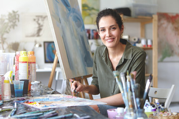 Portrait of gorgeous excited young brunette female artist in casual blouse of khaki color, mixing oil paint on palette using painting knife, passionate about her occupation and process of creation