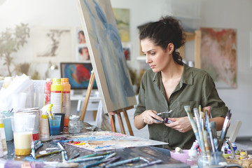 Young female painter sitting at table surrounded with various paint brushes and watercolors while creating beautiful picture on easel. Creative worker working on canvas. Craft and art concept