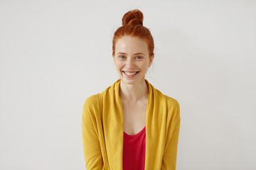 People, lifestyle, positive emotions, fun, joy and happiness concept. Picture of attractive adorable young red-haired female with freckles dressed casually,ac smiling broadly, happy with good news.