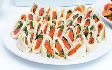 Rolls of thin pancakes with smoked salmon