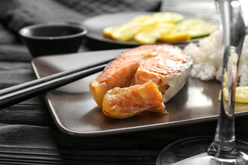Delicious roasted salmon steak with rice on plate, closeup