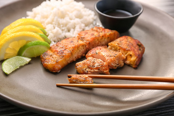 Delicious roasted salmon fillets with rice on plate