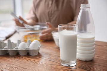 Glass with fresh milk on table and blurred woman on background