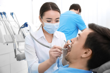 Dentist drilling patient's teeth in clinic