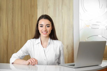 Young smiling receptionist in dental clinic