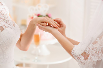 Young lesbian bride putting ring on finger of her future wife