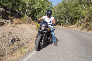 Side view of man sitting on parked custom motorcycle on road in mountains.