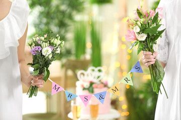 Happy brides holding bouquets of beautiful flowers and garland on lesbian wedding