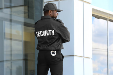 Male security guard standing near big modern building Wall mural