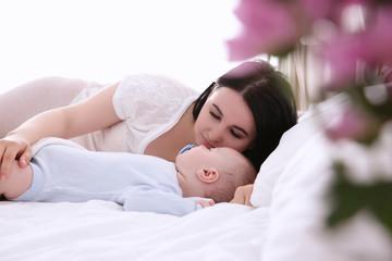 Woman with adorable sleeping baby lying on bed