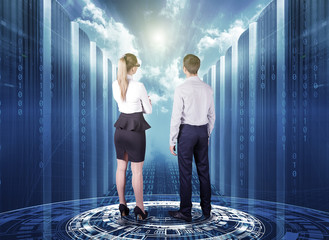 business man and business woman stand on a futuristic hologram and look at the concept of cloud technology among servers in a data center