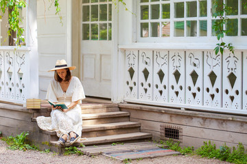woman in a white dress and a straw hat reading a book on the porch of a rural house