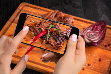 Photographing food concept - tourist takes picture of ready-to-eat beef steak dish on cutting wooden board on smartphone.