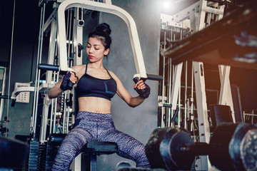 Asian young fitness woman execute exercise with exercise-machine in gym