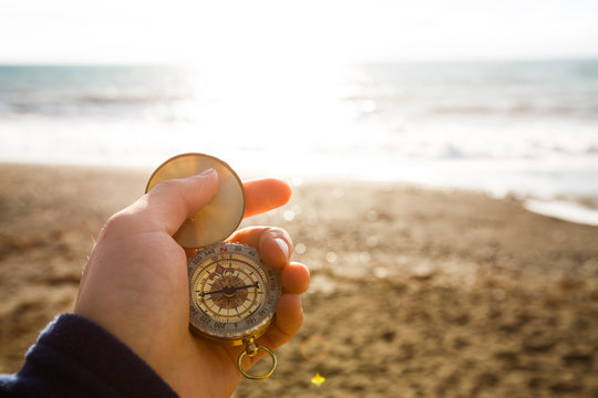 Point of view photo of man holding compass in the hand on the sea and beach background.