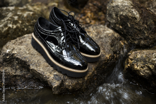 b376a77981d Black shiny patent leather women s brogues shoes on old gray stones ...