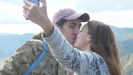 Happy young couple on the mountain top taking selfie photo while kissing