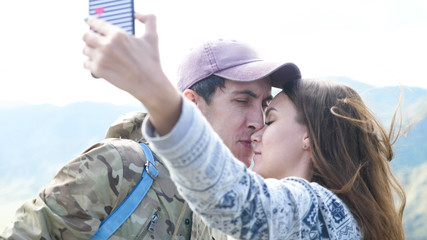 Happy beautiful couple on the mountain top taking selfie photo while kissing