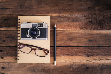 Camera and glasses on notepad on a wooden background,top view